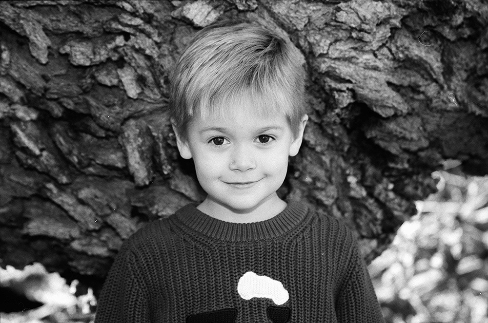 boy-smiling-by-tree